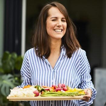 Geneviève O'Gleman qui tient un plateau de légumes crus.