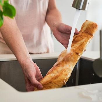 Personne qui passe une baguette de pain sous l'eau d'un robinet de cuisine.