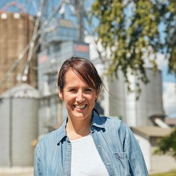Geneviève O'Gleman pose devant une usine de grains située en Montérégie.