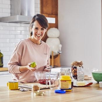 Geneviève O'Gleman dans sa cuisine en train de zester une lime.