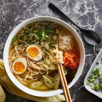 Une soupe aux nouilles dans un bol, contenant des légumes et des oeufs.