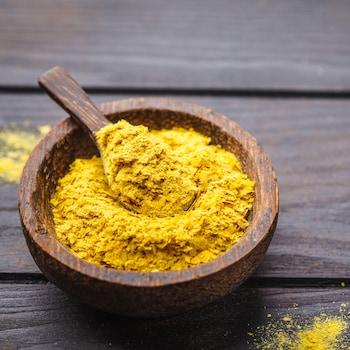 De la levure alimentaire, de couleur dorée, dans un bol sur une table.