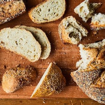 Des morceaux de pain sont déposés sur une planche à découper.