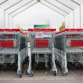 Des paniers d'épicerie sont bien rangés et bien alignés dans l'abri extérieur du supermarché.