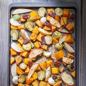 Une plaque de cuisson avec des légumes crus assaisonnés.
