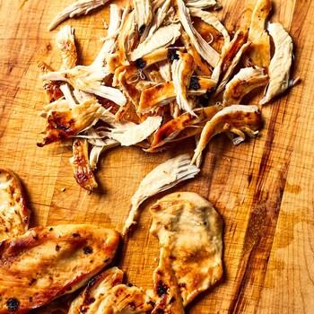 Poulet grillé effiloché sur une planche de bois.