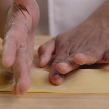 Une personne chasse les bulles d'air et presse la pâte entre deux monticules.