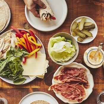Une table garnie de plusieurs assiettes remplies d'ingrédients pour préparer des wraps au poulet, comme des tortillas, de la laitue, du poulet cuit, des épinards et de la mayonnaise.