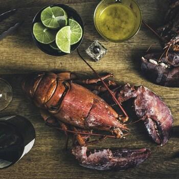 Une table en bois sur laquelle est déposée des homards prêts à décortiquer, des tranches d'agrumes, du beurre fondu et un tire-bouchon.