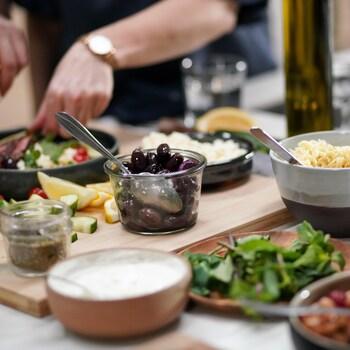 Comptoir rempli de bols d'aliments pour faire un bol-repas : olives, légumineuses, yogourt, fromage...