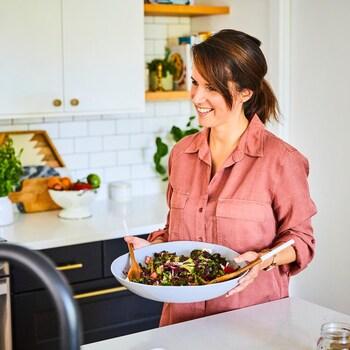 Geneviève O'Gleman tient un grand bol de service contenant une salade colorée.