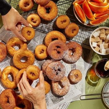 Plusieurs beignes servis avec du café, des cubes de sucre et des quartiers de pamplemousse.