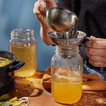 Deux pots en verre remplis de bouillon de volaille.