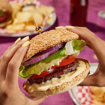 Un burger garni d'oignons rouges, de laitue, de tomates, de viande et d'une sauce blanche.