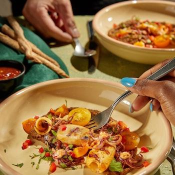 Une assiette colorée de calmars et de légumes grillés.
