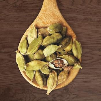 De la cardamome dans une cuillère en bois.