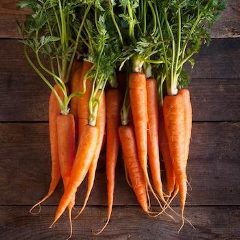 Plusieurs carottes sur une table en bois.