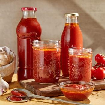 Cinq contenants en verre remplis de coulis de tomate.