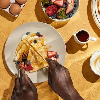 Deux assiettes remplies de crêpes, des fruits, du sirop d'érable et des mains qui coupent des crêpes avec des ustensiles.