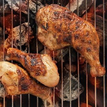 Des cuisses de poulet qui grillent sur du charbon de bois.