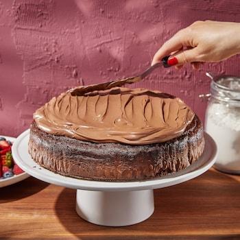 Un gâteau au chocolat sur un présentoir en train de se faire couvrir de glaçage au chocolat.