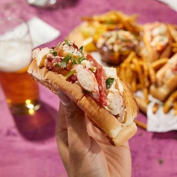 Une main tient un pain hot-dog farci de homard, en arrière-plan, un plateau de frites et de guédilles de homard.
