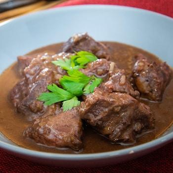 Joue de bœuf dans une sauce au vin rouge sur une nappe rouge.