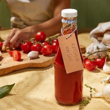 Des tomates en train de se faire couper et une bouteille remplie de ketchup maison.