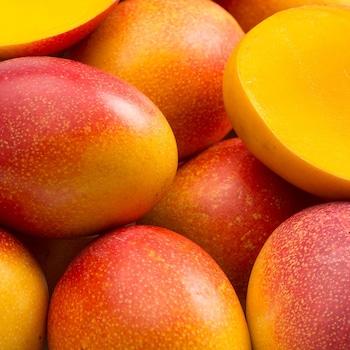 Des mangues oranges entières et des mangues tranchées en deux.