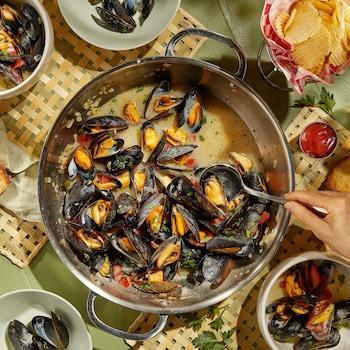 Une grosse casserole remplie de moules avec une cuillère faisant le service.