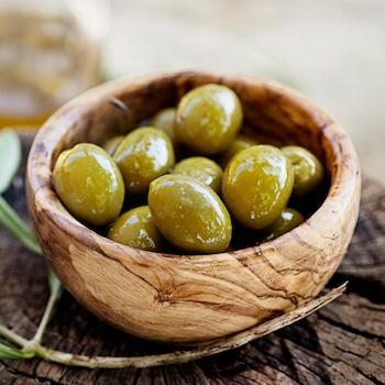 Un bol en bois rempli d'olives vertes, avec une branche d'olivier.