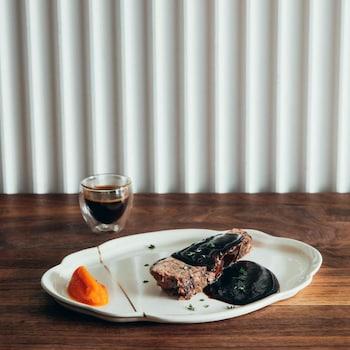 Une assiette avec une pièce de boeuf nappée de sauce, servie aux côtés d'un verre de café espresso et de purée de carottes