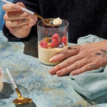 Une panna cotta dans une verrine garnie de fraises, de framboises et de bleuets.