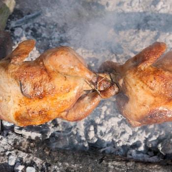 2 poulets entiers qui cuisent sur une broche au dessus d'une braise fumante.