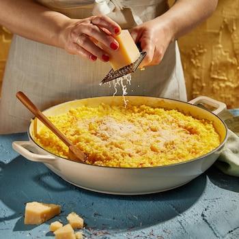 Un plat de risotto sur lequel on ajoute du fromage râpé.