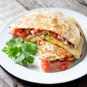 Un sandwich grillé garni de jambon, fromage et tomates.