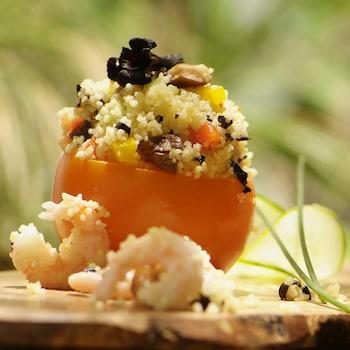 Une taboulé aux champignons noirs et aux crevettes dans un bol en tomate.