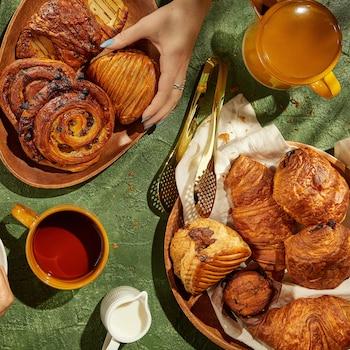Plusieurs viennoiseries dans des assiettes sur une table.