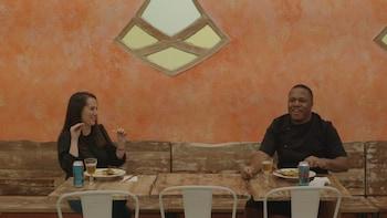 Deux personnes mangent à deux mètres de distance des plats.