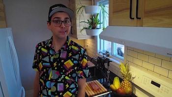 L'animateur, Jérémie est debout dans une cuisine  et parle à la caméra.