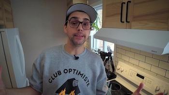 L'animateur est debout dans une cuisine et parle à la caméra.