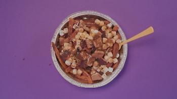 Une sauce au caramel couvre des guimauves, des tranches de patates douces et des morceaux de biscuits au chocolat.