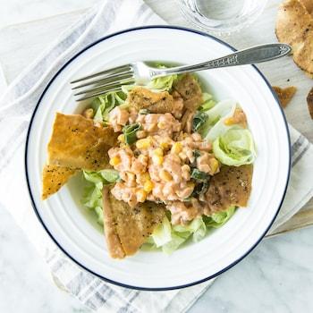 Une salade de tartare de saumon épicé, maïs et chips de pita dans une assiette vue de haut.