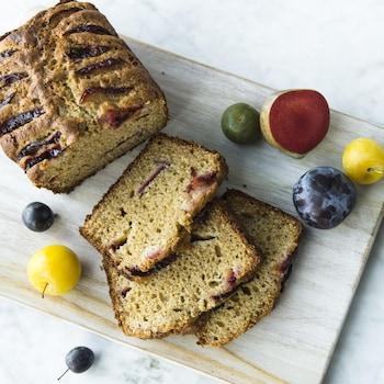 Un cake aux prunes tranché accompagné de prunes de tailles et de couleurs différentes sur une planche de bois vu de haut.