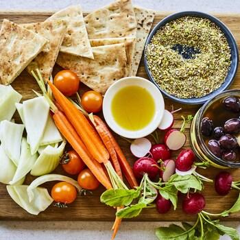 Sur une planche en bois : des carottes pelées, des olives Kalamata, des radis, des pitas grillés et des branches de fenouil forment un cercle autour d'un petit bol d'huile d'olive.