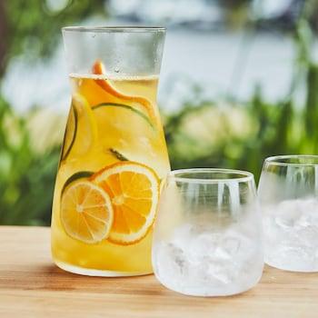 Un récipient avec de l'agua fresca aux agrumes et deux verres avec des glaçons.