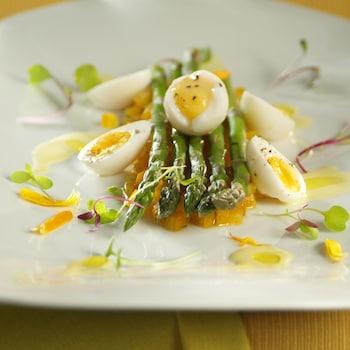 Asperges, tomates jaunes, oeufs de caille poché et émulsion de parmesan dans une assiette.