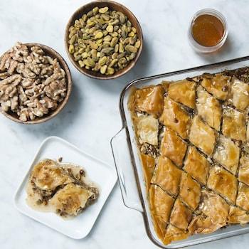 Des baklavas fraîchement sortis du four, avec des bols de noix et de miel.