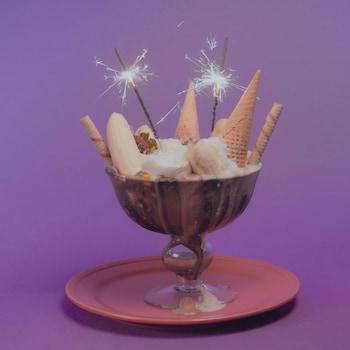 Une banane royale (banana split) garnie de crème fouettée, de bonbons et de cornets à crème glacée, avec des chandelles de type feu d'artifice.