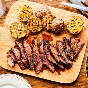 Une planche de bois avec des morceaux tendres de bavette et des pommes de terre grillées.
